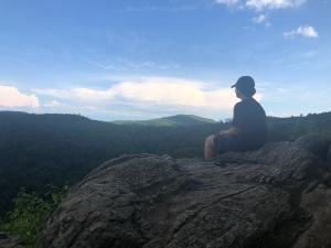 Boy sitting at Hazel Mountain Overlook, Skyline, Dr, Blue Ridge Mountains, VA